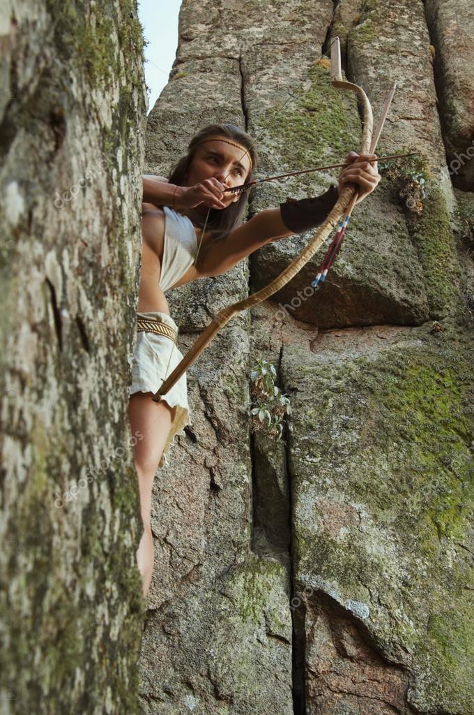 255fee1c4 Mujer primitiva de pie sobre una roca y sosteniendo un arco. mujer ...