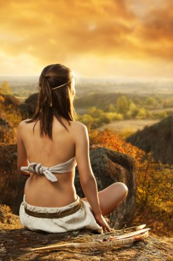 Primitive woman sitting on a rock at the sunset. Amazon woman