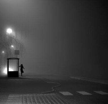 Girl at bus stop at night