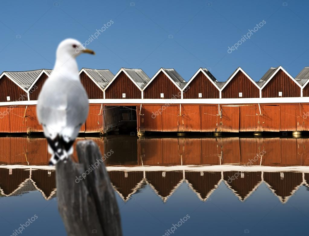 Boat houses reflected in water