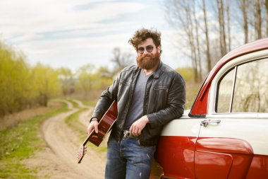 Bearded man playing guitar outdoors near retro car