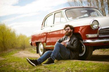 Bearded man playing guitar outdoors near retro car