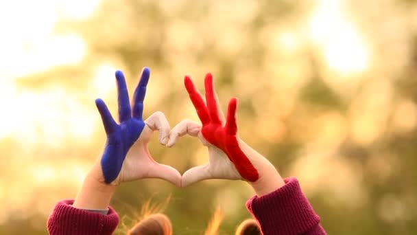 Love and happiness concept. Cute child forming heart gesture with hands outdoors on nature sunset bokeh background. Heart shape of kids hand painted in france flag colors, childrens love concept.