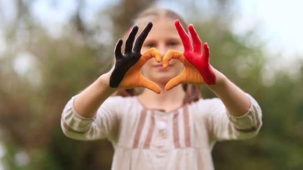 Kid hands painted in Belgium flag color show symbol of heart and love gesture