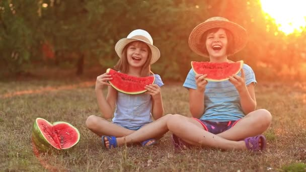 Two preschool smiling child sister eating watermelon at summer park with sunset