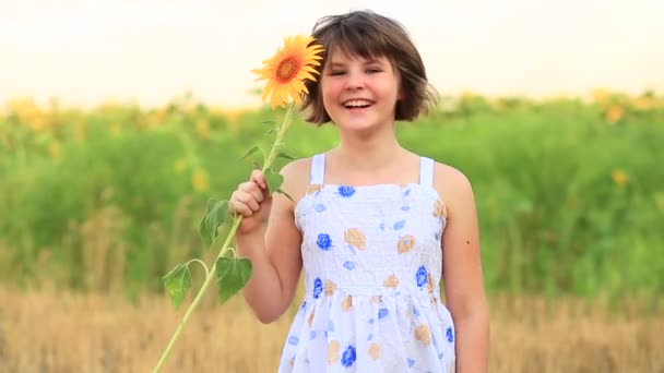 Adorable happy girl holding sunflower and laugh on summer field. Beautiful cheerful teenage girl posing between yellow sunflowers