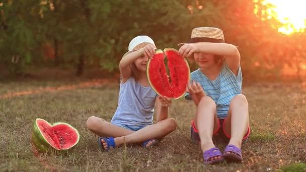 Két óvodás mosolygós húga görögdinnyét eszik a nyári parkban naplementével.