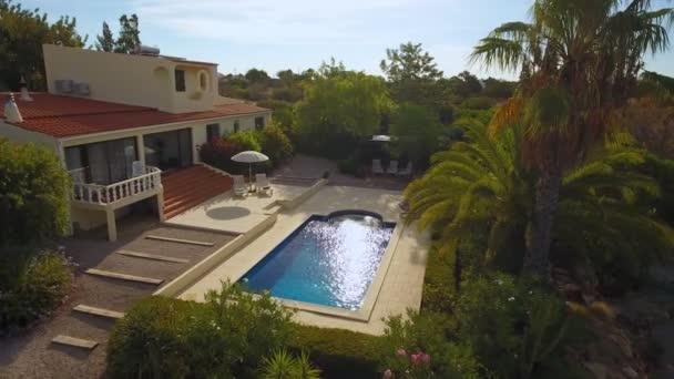 Luxus-Haus mit Pool und Garten mit verschiedenen Arten von Bäumen. Zwei Sonnenliegen zum Sonnenbaden