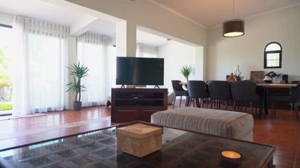 Modernes Wohnzimmer mit Fernseher mit Blick auf den Pool und den Garten. Erstellt mit Wohnkomfort für Kunden.
