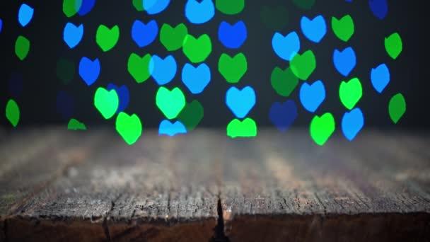 Copyspace záběr prázdné rustikální tabulky propagovat reklamu nebo produkt na Valentines Day. V pozadí, rozmazaná světla, bokeh srdcí blikají.