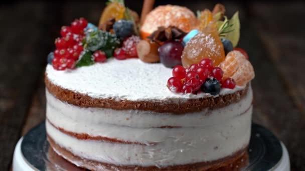 Slavnostní novoroční dort zdobený všemožnými druhy ovoce točící se na otočném stojanu.