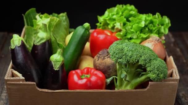 Egy doboz friss zöldséggel, sötét háttérrel, fa vintage asztallal. Nagyításban.