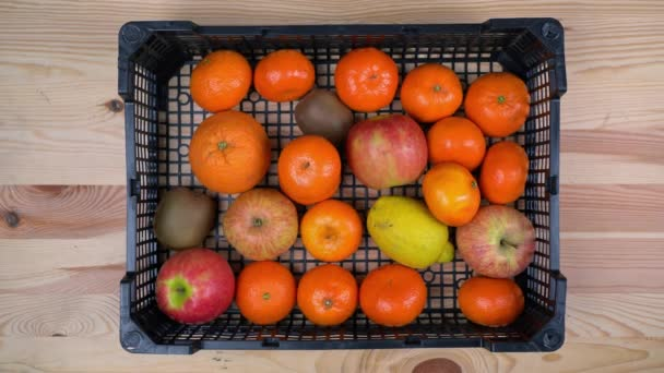 Člověk dává exotické ovoce do krabice, aby doručil potraviny během pandemie. Pomáhat chudým. Plocha.