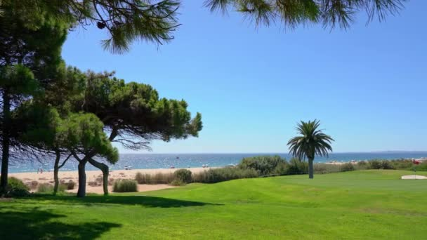 Panning shot from shot nice looking trees and a beach to the green golf field in Vale do Lobo, Portugal.