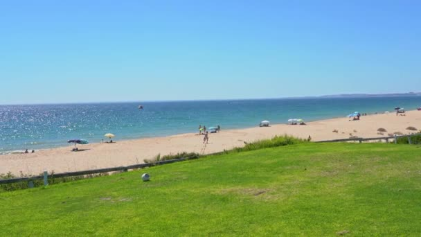 Grassy field near a pleasant looking beach and glistering ocean water in Vale do Lobo, Portugal.