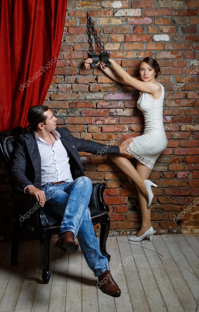 В кандалах. Человек в кресло и женщина в кандалы в комнате