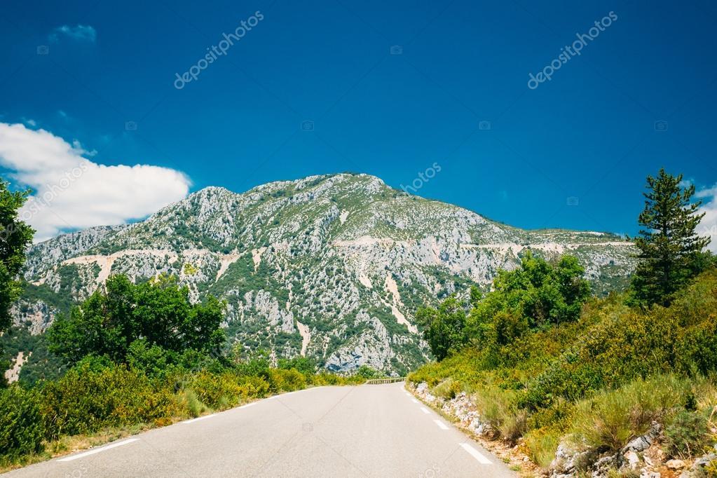 Beautiful asphalt mountain road under sunny blue sky