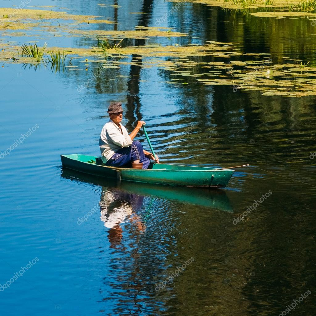 Elderly Man Fishing On River Boat