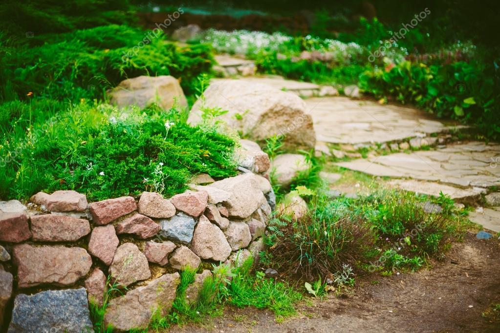 Jardin paysager de conception. Lit de fleur, vert des arbres ...