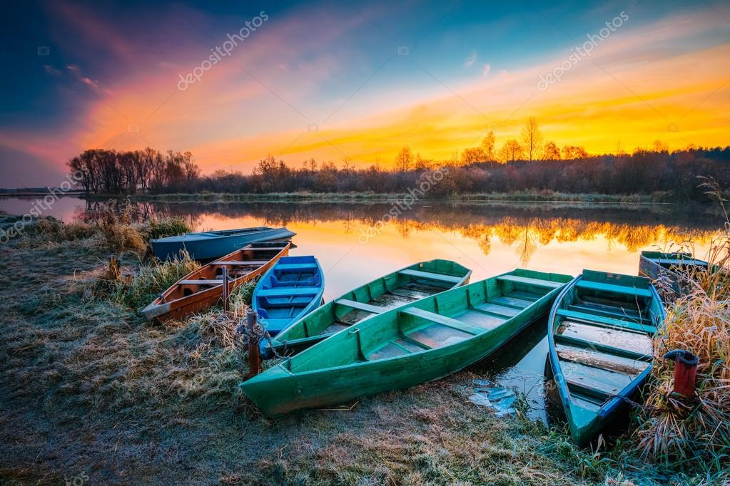 River and old wooden rowing fishing boat at beautiful sunrise in