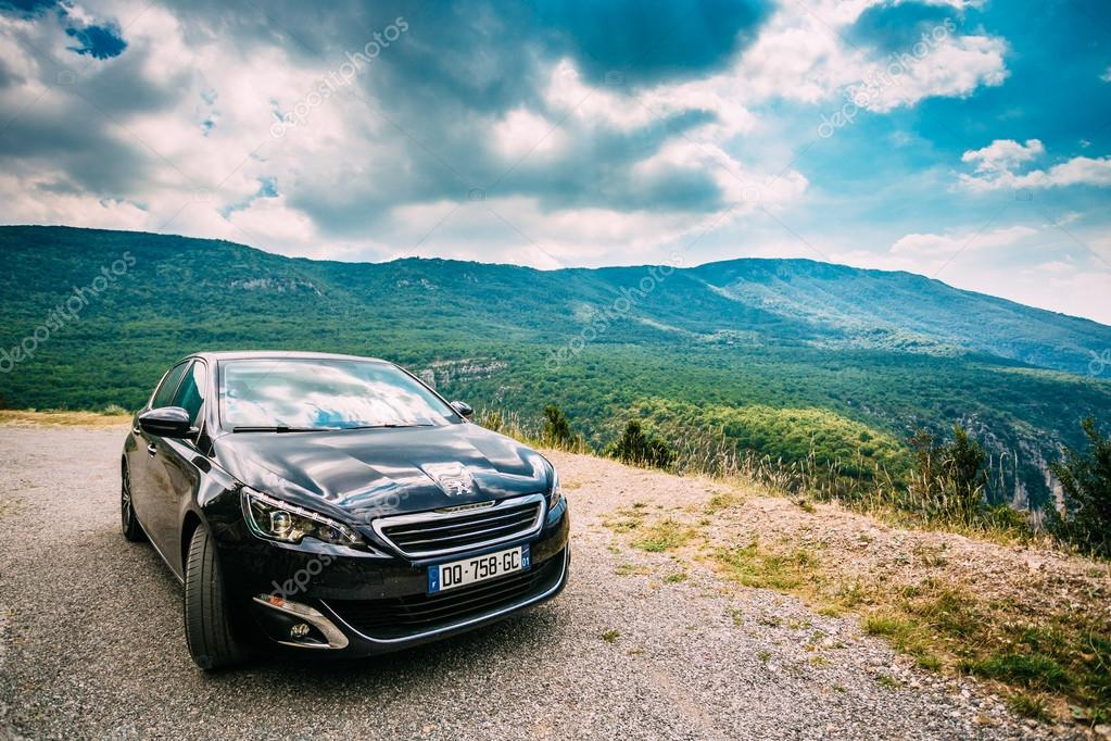 Black colour Peugeot 308 car on background of French mountain na ...