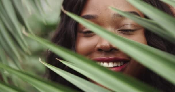 The face of a girl with clean skin with natural makeup among exotic plants, a young African American woman. Advertising of natural and organic cosmetics. Girl look through big green leaves. Smile at