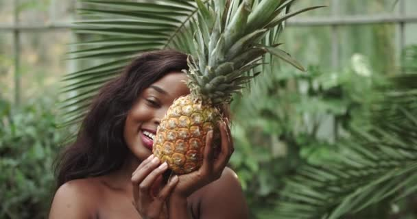 Young beautiful girl with natural makeup holds a pineapple in her hands and smiles at the camera. Against the background of tropical forest and wildlife. The girl covers her face with a pineapple. The