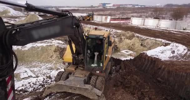 Raupenbagger auf der Baustelle. Baumaschinen zum Ausheben, Beladen, Heben und Schleppen von Fracht auf Baustellen. Luftaufnahme von oben, 4K-Video