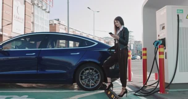 Krásná evropská obchodní žena, spoléhá na modré luxusní elektrické auto, které je nabíjení. Elektrický nabíjecí kolík. Luxusní elektromobil nabíjí. Práce při nabíjení elektrického auta. Usmívající se dívka