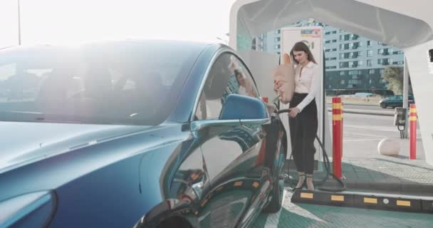 Krásná obchodní žena se blíží její elektrické auto s potravinami a vypadá na kameru, usmívá se. Nabíjení elektromobilů. Ekologicky šetrná doprava. Automatické nabíjení dokončeno. Nakupování