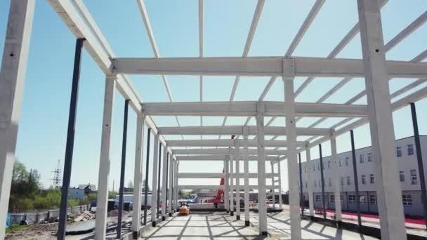 Rahmen auf der Baustelle des Büros für moderne Architektur oder Geschäftsgebäude aus Stahlbeton. Flug über die Baustelle. Träger mit Stahlbewehrung von oben.