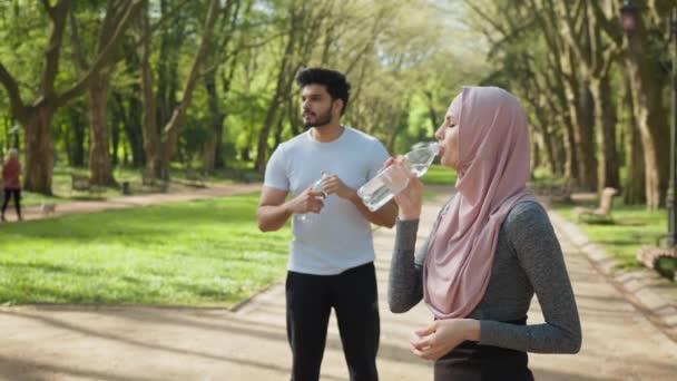 Boční pohled na atraktivní žena v hidžábu pitné vody, zatímco hezký arabský chlap stojí za. Mladý pár ve sportovním oblečení relaxaci po cvičení na čerstvém vzduchu. Arabská rodina v parku s vodou