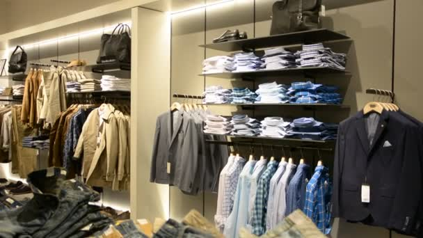 Mladý muž výběr oblečení v obchodě