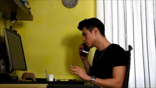 Young man working at home with computer, cell phone and table, smoking cigarette