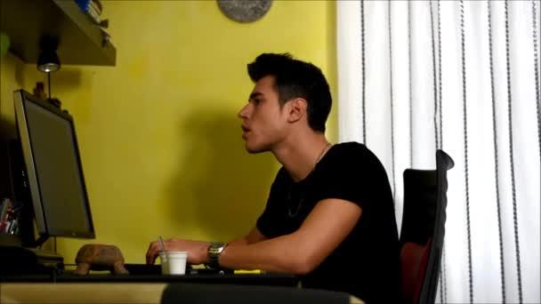 Fiatal férfi ül otthon használ a számítógép, a dohányzás cigaretta