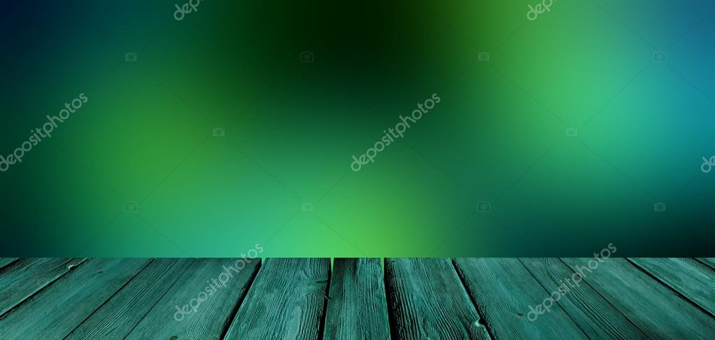 Deep dark green blur background of the coming dusk or the dark forest. Green rustic wooden table in the foreground.