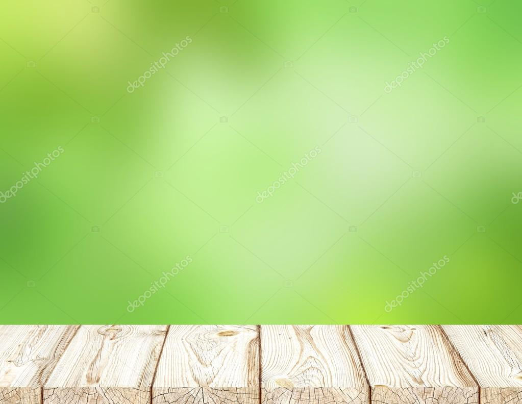White boards to form a table or wood flooring. Bright green blur background fresh summer forest.