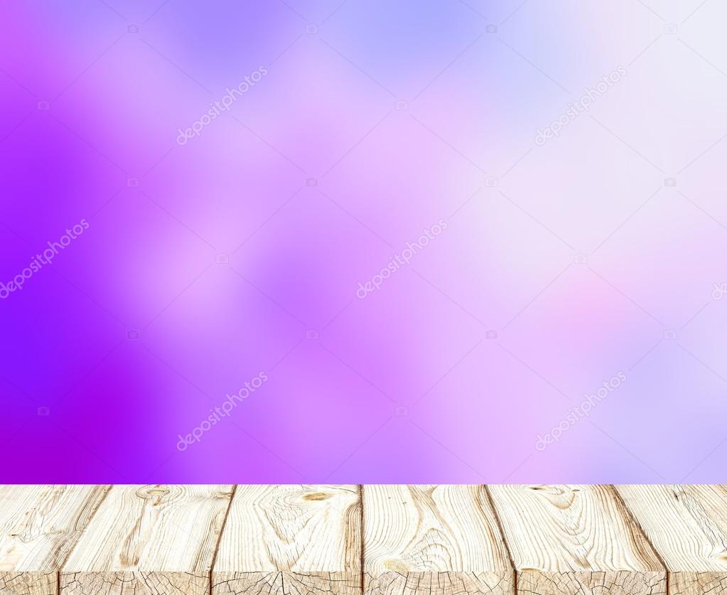 Soft romantic purple haze to blur the background. Blooming lilac bushes. Bright wood surface textu