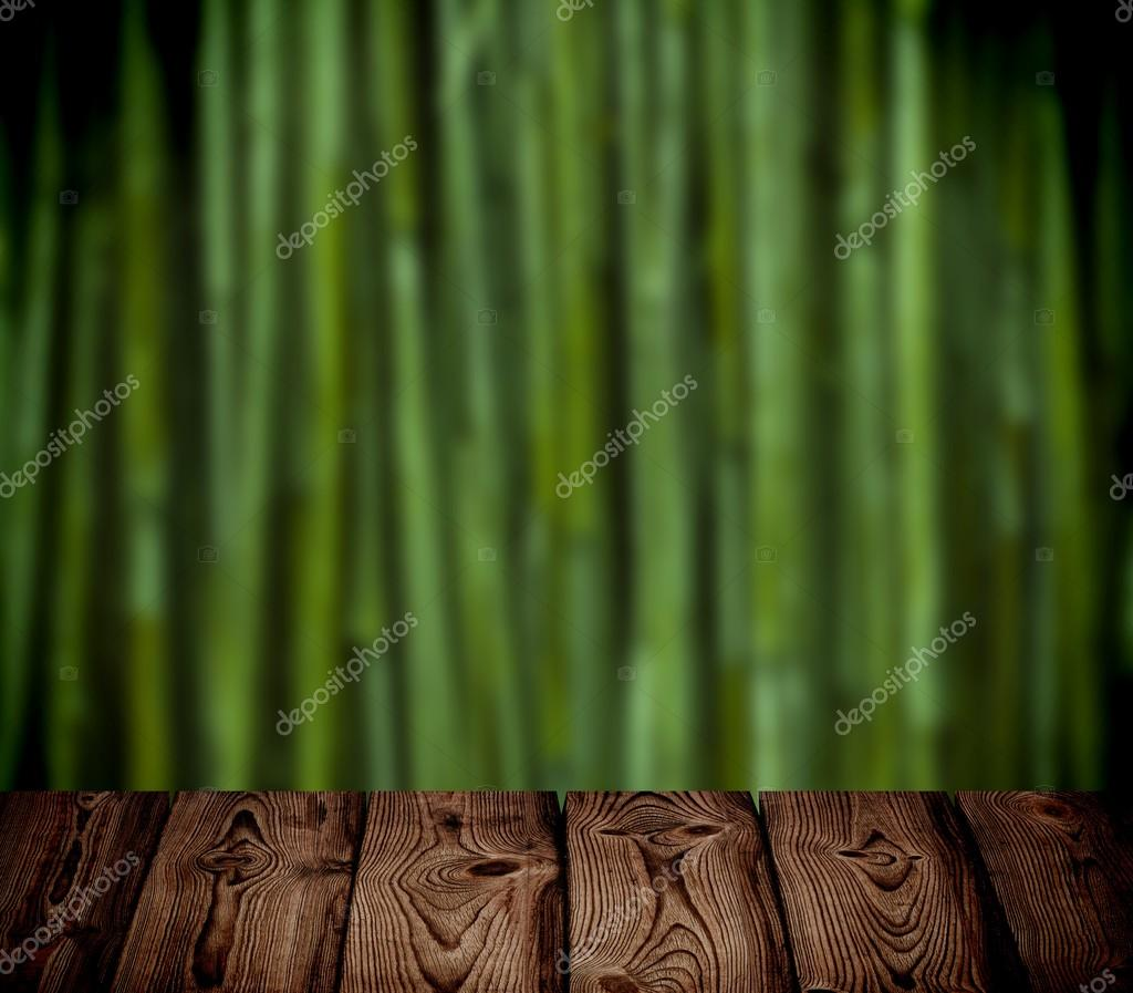 Brown wooden table on the green bamboo forest blur background.