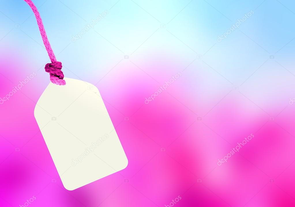 Cardboard label on the spring blooming garden blur background. Blossoming cherry trees under a bright blue sky.