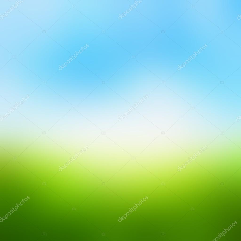 Green field under blue sky blur background. Matte texture gradually becomes green grass in the bright blue sky. Spring background. Summer background.