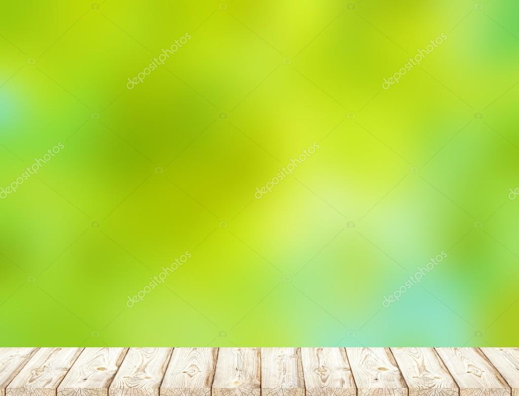Light spring greens blur the background. Light wood texture of the table or bench in the garden or ark.