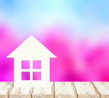 Little paper house is on the wooden surface of the table or floor. Behind a blooming spring garden blur background. Like cherry or apple trees. The blue cloudless sky. Housing in the fresh air.