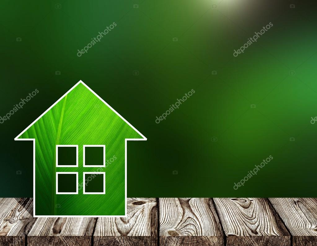 Small house made of green leaf. Light gray wooden boards to form a flat surface of a table or bench. Deep green matte blur the background. Environmentally friendly housing in the nature, outside the city. Summer forest background.