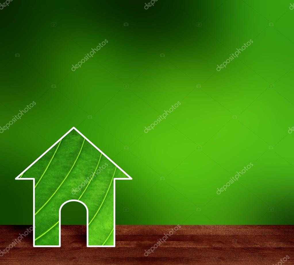 Green house made from fresh leaf. Brown wooden smooth surface of a table or bench in the garden. Gentle deep greens blur background.