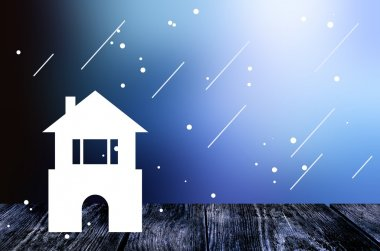 House is defenseless in bad weather. Little house on the wood surface. Cold sleet and wind. Dark blue blur background.