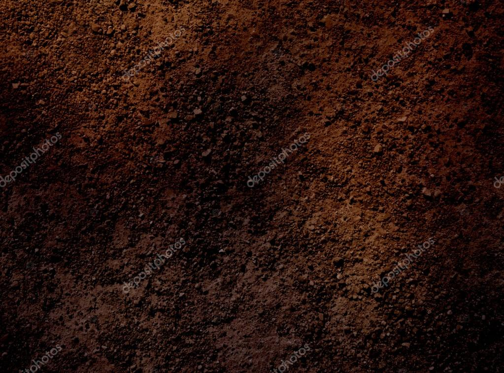 Dark brown surface of dry soil. The texture of the earth partially lit and partially in shade.