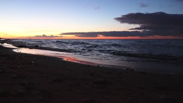 Farbenfroher Sonnenaufgang am Meer mit Zirruswolken am Himmel. Die ersten Sonnenstrahlen werden in Wasserwellen reflektiert. Ostsee, Finnischer Meerbusen, Sankt Petersburg, Russland, 4k