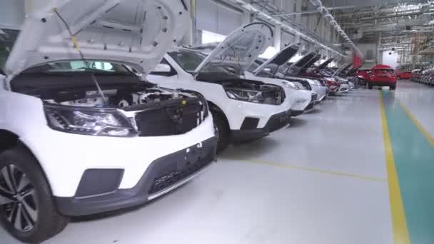 Řada nových lesklých osobních automobilů v továrně připraven export nebo dovoz přes moře. Mnoho podobných nových moderních lesklých vozů stojí na výstavě v řadě na prodej bez lidí. Pracovníci a automobily 4k