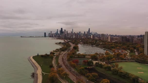 Beautiful panning aerial panoramic view of Chicago skyline with vehicles traveling on Lake Shore Drive through Lincoln Park passing by Diversey boat harbor and Lake Michigan with clouds in sky above.